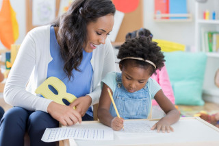 Child-care-worker-helps-little-girl-with-handwriting-886934186_6720x448_20200610-124753_1